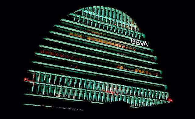 El edificio La Vela de BBVA iluminado de color verde.