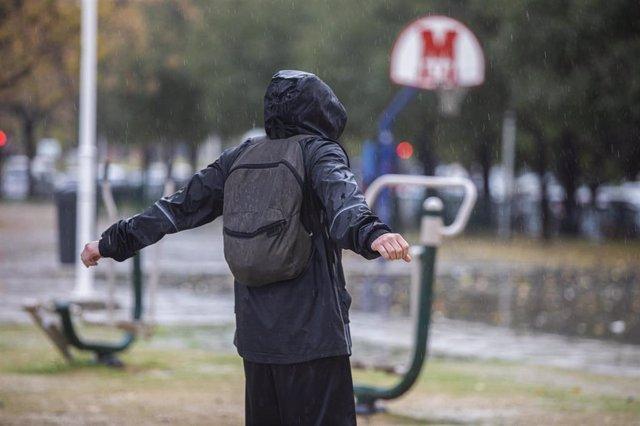 Archivo - Una persona con un chubasquero bajo la lluvia. Las ciudades andaluzas Córdoba, Sevilla, Huelva, Cádiz y Málaga tienen hoy aviso amarillo por acumulaciones de las precipitaciones que podrán llegar a los 25 litros por metro cuadrado en una hora. E