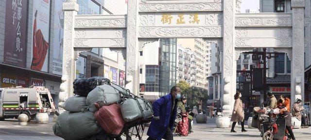 Archivo - Un vendedor en la entrada de Han Zheng Jie, una zona peatonal de Wuhan, China, en enero de 2021.