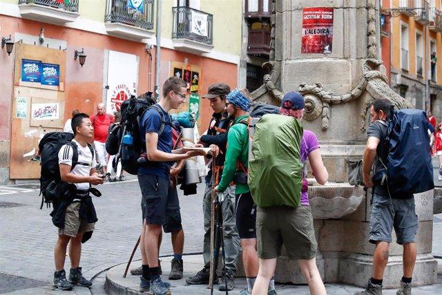 Archivo - Caminantes del Camino de Santiago beben de una fuente a su paso por Pamplona