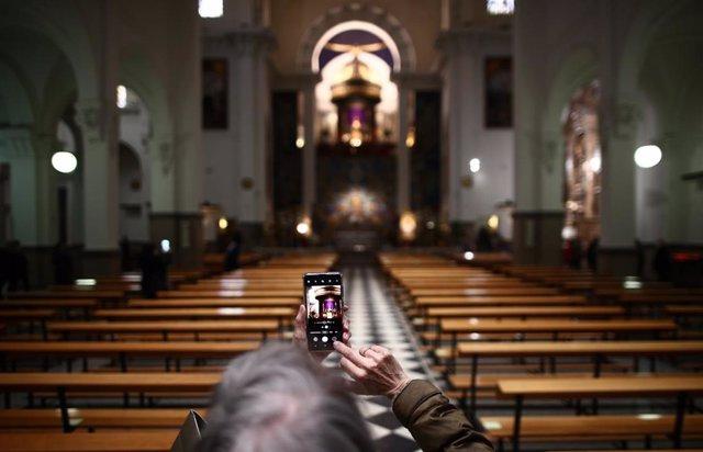 Una devota toma una foto de Jesús de Medinaceli durante el segundo año que se suspende el tradicional besapiés por riesgo de contagio de coronavirus