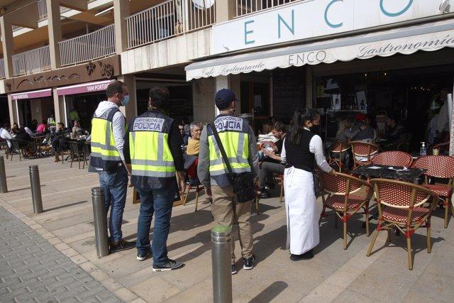 Varios agentes de la Policía Nacional durante un control a una terraza de un restaurante de Palma de Mallorca (España), a 6 de marzo de 2021.