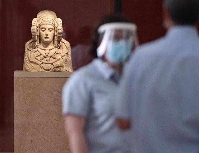 Archivo - Dos trabajadores protegidos con mascarilla y pantalla vigilan una de las salas donde se encuentra la escultura de La Dama de Elche en el Museo Arqueológico.