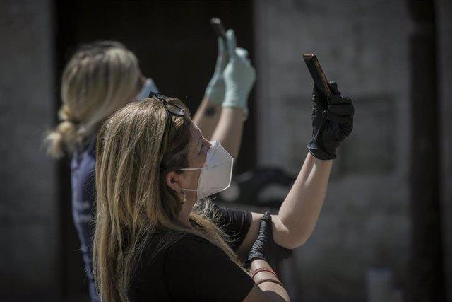 Archivo - Dos personas protegidas con mascarillas y guantes graban con sus móviles  durante el estado de alarma. En Sevilla (Andalucía, España), a 10 de abril de 2020.
