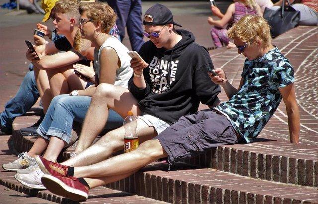 Jóvenes mirando teléfono móvil