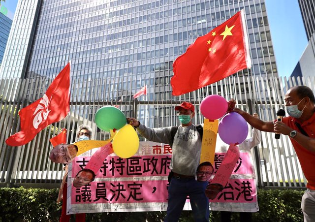 Archivo - 12 November 2020, China, Hong Kong: Pro-government members hold balloons with papers faces of the four ousted lawmakers as they celebrate outside the legislative council the resignation of pro-democratic legislators. 15 lawmakers resigned en mas
