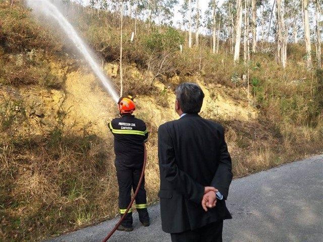 Archivo - El jefe de la agrupación de Protección Civil apaga un incendio mientras Revilla le observa, días antes de ser acusado como presunto autor del incendio de La Alcomba