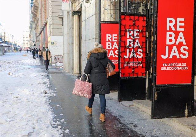 Archivo - Una mujer pasa por delante de un establecimiento durante el séptimo día de las rebajas de invierno, en Madrid