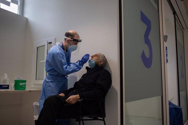 Un home se sotmet a una prova PCR a l'edifici Garbí-Vall d'Hebron, a Barcelona.