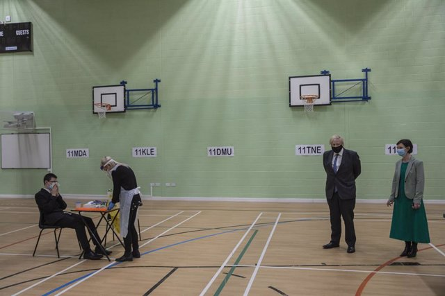 23 February 2021, United Kingdom, London: British Prime Minister Boris Johnson (2nd R) stands in the gym, which is being used as a makeshift coronavirus testing centre for students, during a visit to Sedgehill School. Photo: Jack Hill/The Times via PA Wir