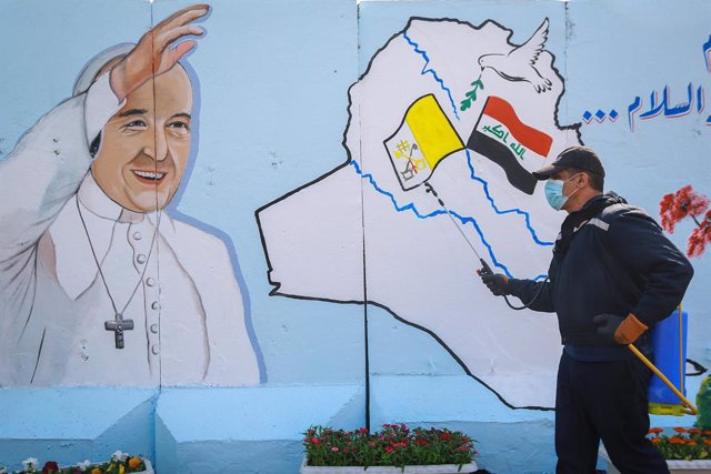 02 March 2021, Iraq, Baghdad: An Iraqi civil defense worker sprays disinfectant in front of a mural depicting Pope Francis in the Syriac Catholic Church of Our Lady of Salvation in Karrada district. Pope Francis is scheduled to visit Iraq from 05 to 08 Ma