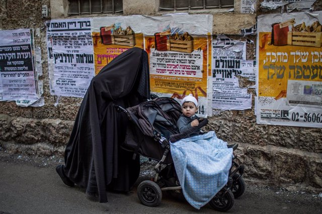 28 February 2021, Israel, Jerusalem: An Ultra Orthodox Jewish woman covered wearing a Haredi burqa pushes a baby stroller during the celebrations of the Jewish holiday of Purim at Jerusalem's Mea She'arim neighbourhood.  Purim, also called the Festival of