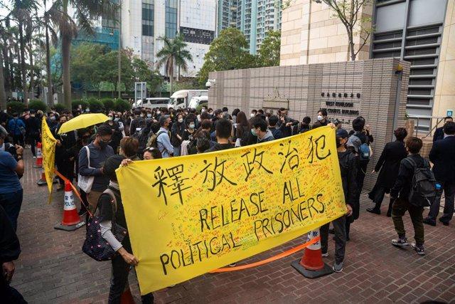 Manifestantes protestan a las puertas del tribunal en el que 47 activistas prodemocracia están siendo juzgados en Hong Kong.