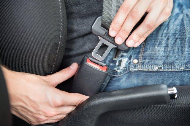 Una persona se abrocha el cinturón de seguridad.