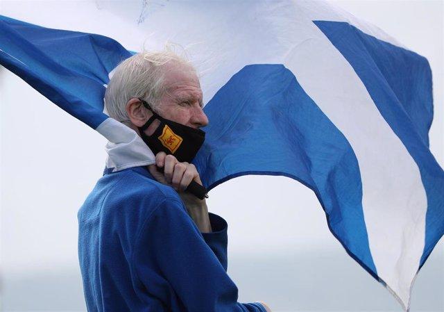 Archivo - Un hombre con mascarilla portando la bandera de Escocia durante una manifestación independentista