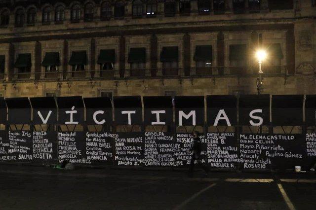 Homenaje a víctimas de violencia machista en la valla levantada en el Zócalo de Ciudad de México con motivo del Día de la Mujer