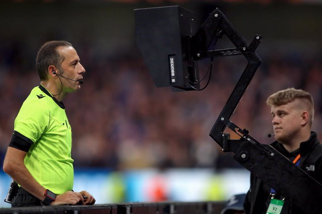 Archivo - 17 September 2019, England, London: Referee Cuneyt Cakir (L) checks the pitch side tv camera to check a VAR decision before awarding a penalty during the UEFA Champions League Group H soccer match between Chelsea and Valencia at Stamford Bridge.