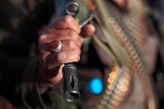 Archivo - Simpatizante huthi empuña un fusil de asalto