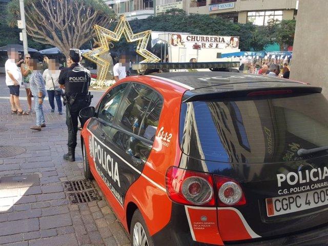 Archivo - Agente de la Policía Canaria junto a un coche patrulla