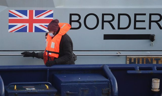 27 February 2021, United Kingdom, Dover: A group of people thought to be migrants are brought in to Dover by Border Force officers following a small boat incident in the English Channel. Photo: Gareth Fuller/PA Wire/dpa