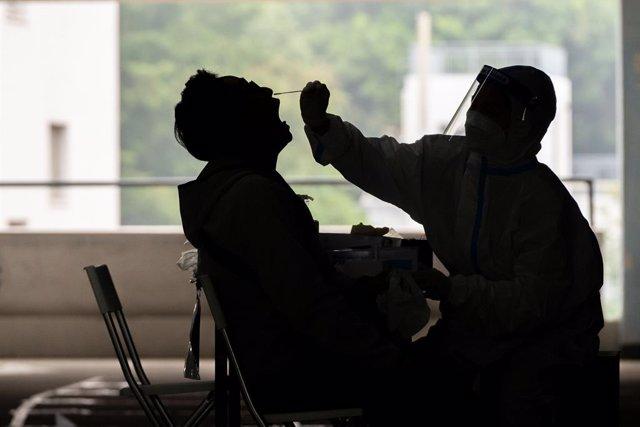 Archivo - 12 December 2020, China, Hong kong: A health worker takes a swab sample from a man at a Covid-19 testing centre in Hong Kong. Photo: Geovien So/SOPA Images via ZUMA Wire/dpa