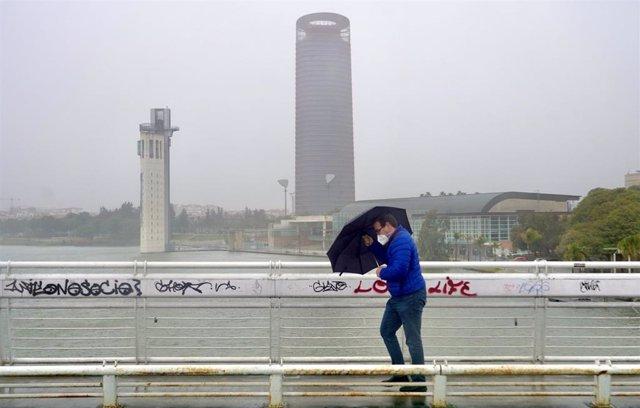 Un persona se protege de la lluvia y el viento caminando por la pasarela  peatonal de la Cartuja en Sevilla