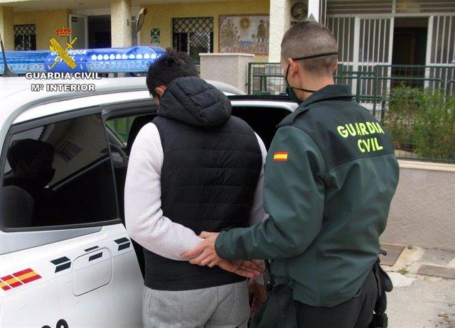 Un agente de la Guardia Civil con uno de los detenidos