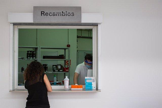 Archivo - Un empleado atiende a una clienta en un concesionario.