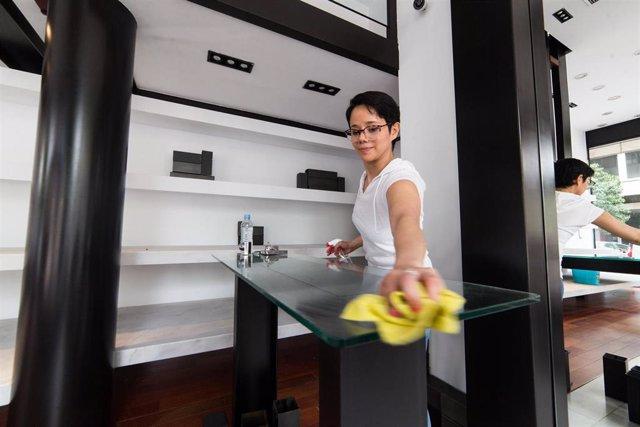 Archivo - Una mujer limpia una mesa de su negocio