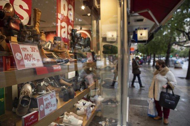 Archivo - Cartel anunciando descuentos en un zapatería durante el comienzo de las rebajas de invierno en Sevilla