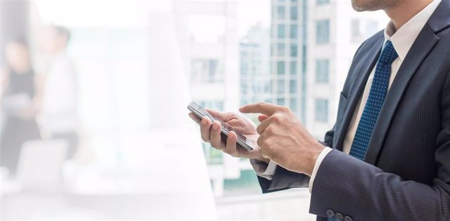 Un ejecutivo mirando su teléfono móvil