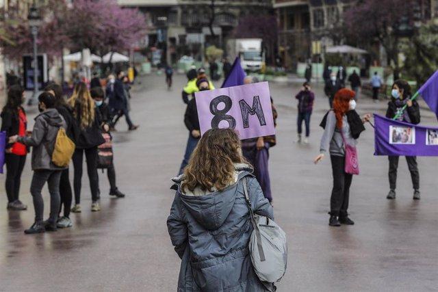 Una de las participantes sostiene una pancarta en la concentración convocada por la Assemblea Feminista en la plaza del Ayuntamiento de Valencia con motivo del 8-M