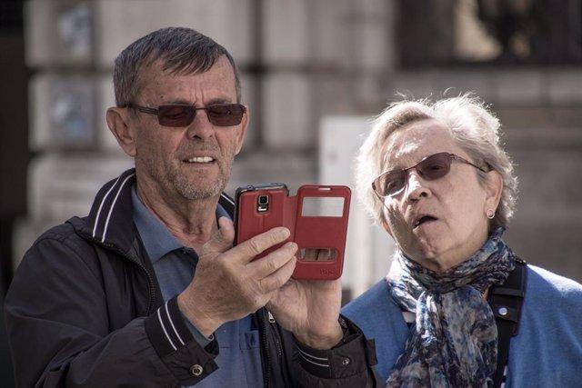 Dos ancianos observan un teléfono móvil