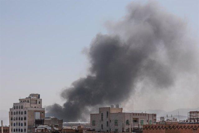 El humo sale de una base milita huthi después de que una serie de ataques aéros fueran lanzados por la coalición internacional contra la capital Saná, controlada por los rebeldes en represalia a un ataque huthi en el país vecino.