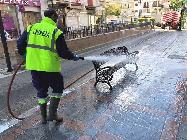 Archivo - Un operario de Fuengirola baldea las calles y el mobiliario de la localidad malagueña con desinfectante ante el coronavirus