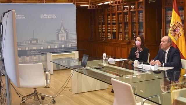 El ministro de Justicia, Juan Carlos Campo, presenta a la magistrada de enlace en Bélgica, Paloma Conde-Pumpido, en una reunión telemática con su homólogo belga, Vicent Van Quickenborne.
