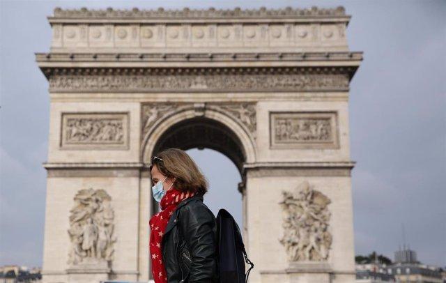 Archivo - Una mujer con mascarilla ante el Arco del Triunfo de París