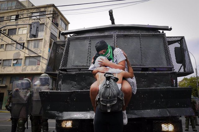 08 March 2021, Chile, Valparaíso: Two women embrace each other in front of a security force vehicle during a demonstration for women's rights on International Women's Day. Photo: Santiago Morales/Agencia Uno/dpa