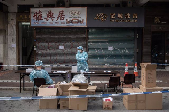 Archivo - FILED - 23 January 2021, China, Hong Kong: Health workers surrounded by boxes wait in an area where am unprecedented lockdown has been declared by the Hong Kong government in order to carry out compulsory Coronavirus (COVID-19) tests. Photo: Iva