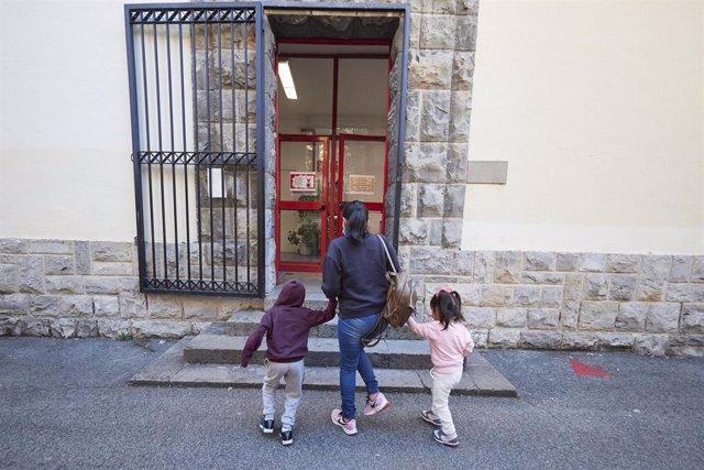 Archivo - Una madre lleva a sus hijos al Colegio.