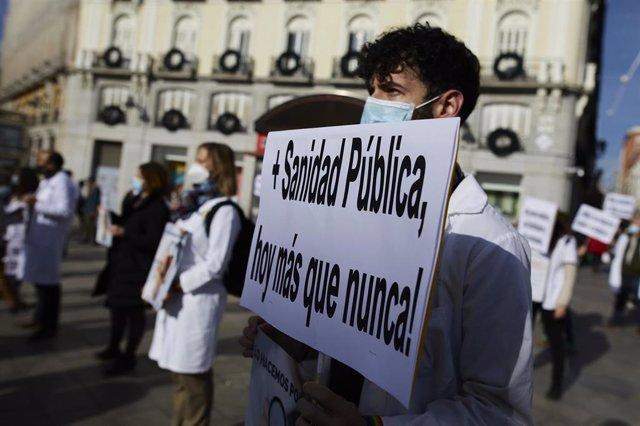 Archivo - Un trabajador sanitario sostiene una pancarta durante una concentración convocada por la Asociación de Médicos y Titulados Superiores de Madrid (AMYTS), en la Puerta del Sol, en Madrid (España), a 24 de noviembre de 2020.