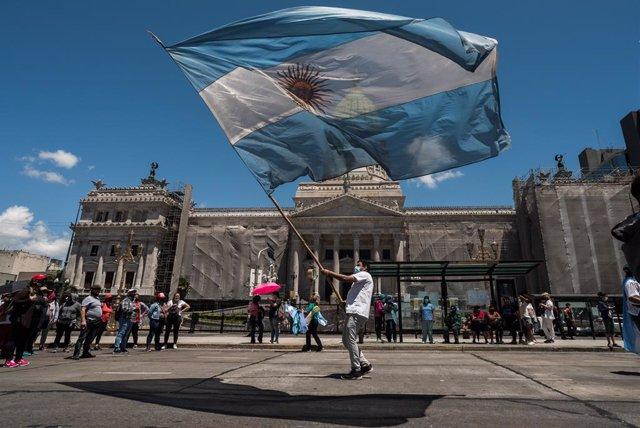 Archivo - Un hombre hondeando la bandera de Argentina en la Plaza de Mayo