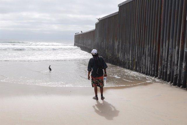 Archivo - Migrante en el muro de separación con EEUU