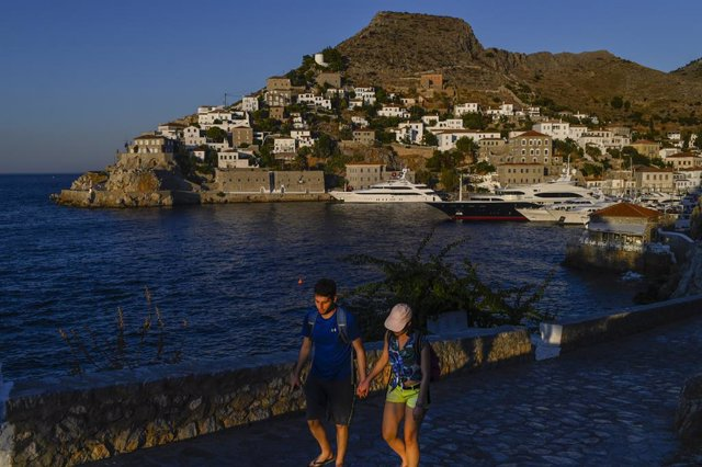 Archivo - 24 July 2020, Greece, Hydra: A couple hold hands as they walk past the harbour in the Greek island of Hydra. Cars, neon signs and plastic chairs are prohibited on Hydra island, which covers almost 50 square kilometres south-west of Athens. Photo