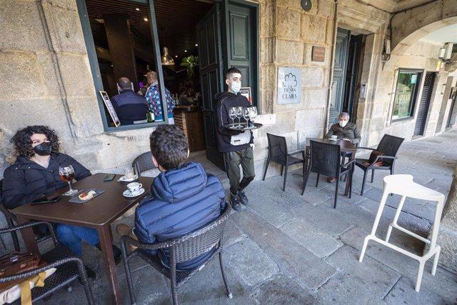 Un empleado trabaja en la terraza de su establecimiento durante el primer día de la reapertura del interior de los bares y restaurantes en Pontevedra, Galicia (España), a 8 de marzo de 2021. Desde hoy la Xunta permite la apertura de las áreas sanitarias d