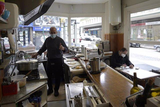 Un empleado trabaja en el interior de su establecimiento durante el primer día de la reapertura del interior de los bares y restaurantes en A Coruña a 8 de marzo de 2021