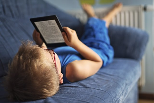 Archivo - Niño con un libro electrónico tumbado en el sofá.