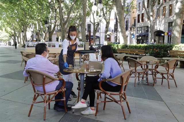 Archivo - 11 May 2020, Spain, Palma: A waitress serves coffee to two guests on the terrace of a bar in Palma, as restrictions imposed to contain the spread of the novel coronavirus are gradually lifted. Photo: Clara Margais/dpa