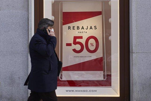 Archivo - Una persona pasa por delante de un establecimiento durante el séptimo día de las rebajas de invierno, en Madrid, (España)