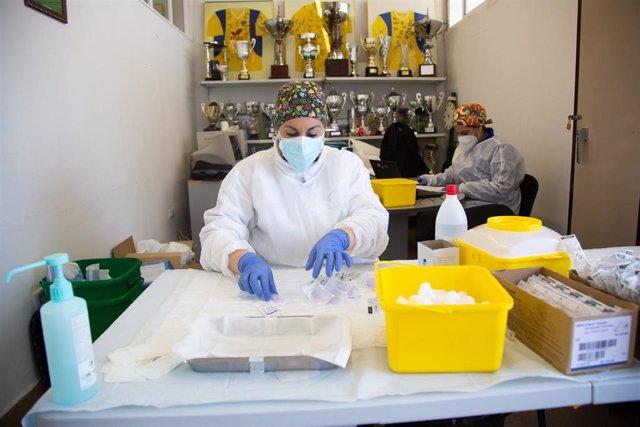 Una sanitaria prepara la dosis de la vacuna de Pfizer polideportivo de Villafranca de los Barros.